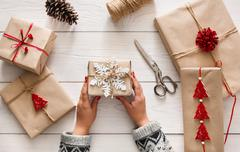 Woman's hands wrapping christmas holiday present with craft twine Stock Photos