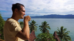 Male traveler drinking coffee and looking at Toba lake from Samosir island Stock Footage