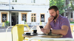 Man makes notes from smartphone to notebook in cafe, slider shot, righ Stock Footage