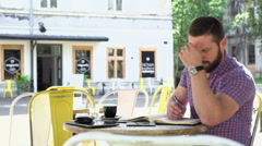 Man makes notes from smartphone to notebook in cafe, slider shot, left Stock Footage