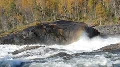 Mighty roaring waterfall in autumn creates rainbow effect in water mist Stock Footage