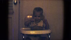 1959: boy in high chair eating and dumping food on the floor smiling DISNEYLAND, Stock Footage