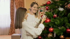 Portrait of daughter helps mother decorating Christmas tree with baubles and  Stock Footage
