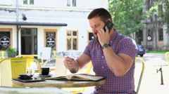 Man talking by smartphone makes notes to notebook, slider shot, left Stock Footage