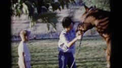 1968: taking their first horse ride and learning to saddle up for safety Stock Footage