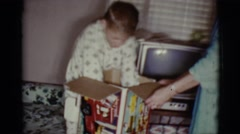 1968: a small boy in pajamas opening a present and pulling a truck from a box Stock Footage