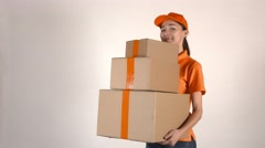 Beautiful girl in orange courier uniform delivering a stack of cartons. Light Stock Footage