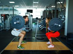 Athletic man and woman with barbell doing squats in the gym Kuvituskuvat