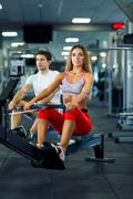 Athletic man and woman doing workout on rowing simulator in crossfit gym Kuvituskuvat