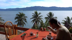 Young caucasian man eating at restaurant with Toba lake view on Samosir island Stock Footage