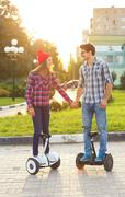 A young couple riding hoverboard - electrical scooter, personal eco transport Stock Photos