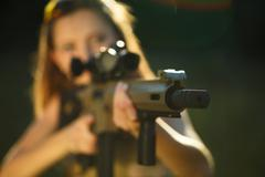 Girl with a gun for trap shooting aiming at a target Stock Photos