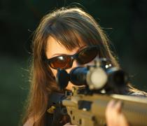 Girl with a gun for trap shooting and shooting glasses aiming at a target Stock Photos
