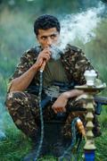 Man in camouflage with a shotgun smokes a hookah outdoor Kuvituskuvat