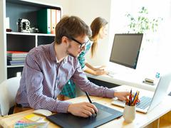 Young artist drawing something on graphic tablet at the office Stock Photos