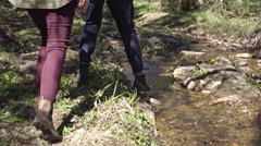 Boyfriend and Girlfriend Jumping over Brook Stock Footage