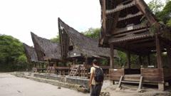 Backpacker male traveler walking around traditional batak village on Sumatra Stock Footage