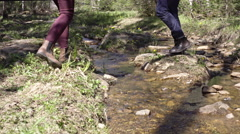 Young Couple Stepping over Little Brook Stock Footage