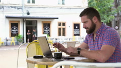 Man ends work on laptop, drinks coffee and smiles for camera in cafe, Stock Footage