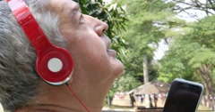 Senior man with headphones listening to music and singing at park Stock Footage