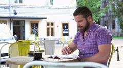 Young man reading book in cafe, slider shot right Stock Footage