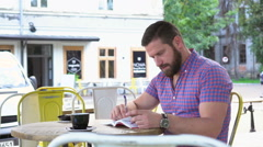 Young man reading book in cafe, slider shot left Stock Footage