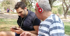 Friends of Different Generations Using Technology in a Park Stock Footage