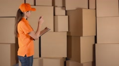 Beautiful female warehouse worker in orange uniform counting items and making Stock Footage