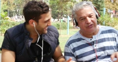 Father and son listening to music and having fun in the park Stock Footage