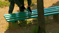 Worker Paints Wooden Bench With Green Paint and Then Sticks Piece of Paper Stock Footage