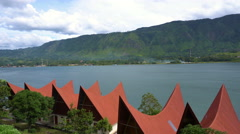 Panorama of Toba lake with traditional batak-style roofs from Samosir island Stock Footage