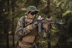Special forces soldier aiming in the forest Stock Photos