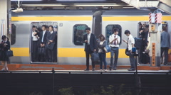 People boarding and exiting trains at a subway station in Tokyo Stock Footage