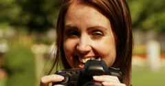 Pretty professional woman photographer with dslr camera taking a picture of you. Stock Footage