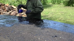 Worker man lays hot tar with gas burner priming on boat bottom. 4K Stock Footage