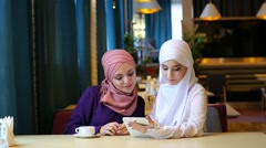 Two Beautiful Muslim Girl Using Tablet In Cafe And Laughing Stock Footage