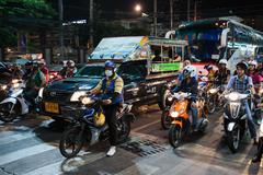 Motorbikes at a crossroads at night in Thailand Stock Photos