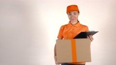 Girl courier in orange uniform delivering a big carton. Light gray backround, 4K Stock Footage
