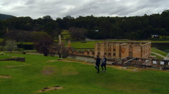 Couple walking in the penal site open air museum at Port Arthur in Tasmania Stock Footage