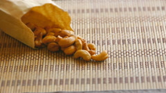 Cashew nuts lying on a bamboo napkin on the table, close-up Stock Footage