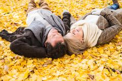 Active senior couple in autumn park lying on the ground Kuvituskuvat