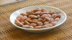 Almonds are in a saucer on the table, close-up on a circle Stock Footage