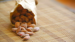 Almonds are on the table, poured out of a paper bag, close-up Stock Footage