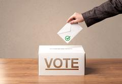 Close up of male hand putting vote into a ballot box Stock Photos