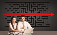 Business couple with a solved puzzle in background Kuvituskuvat