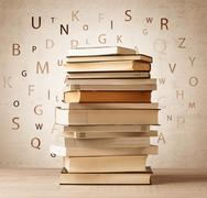 Books with flying letters on vintage background Kuvituskuvat