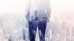 Business man standing on roof with city in the background Stock Photos