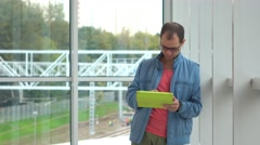 Programmer in black rim glasses using his tablet computer at modern railroad Stock Footage