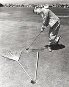 Caught between a rake and a gardening fork on the putting green Stock Photos