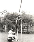 Man on stilts holding onto giant golf club with woman seated on it Kuvituskuvat